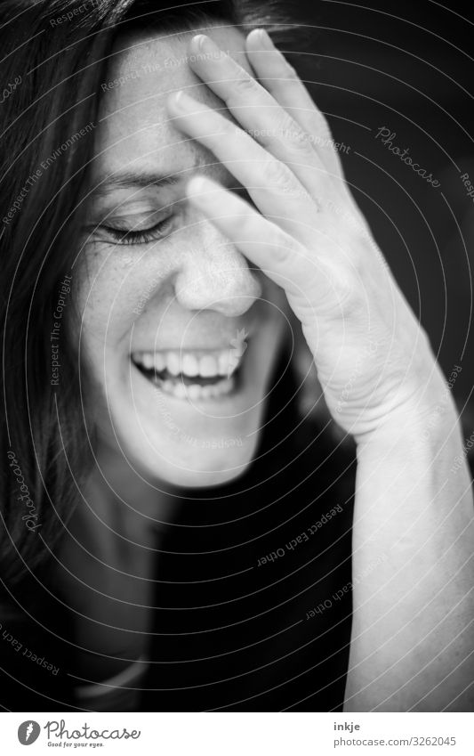 laughing woman with closed eyes and hand on forehead Black & white photo Interior shot portrait Close-up portrait of a woman shut eyes Laughter cheerful Amused