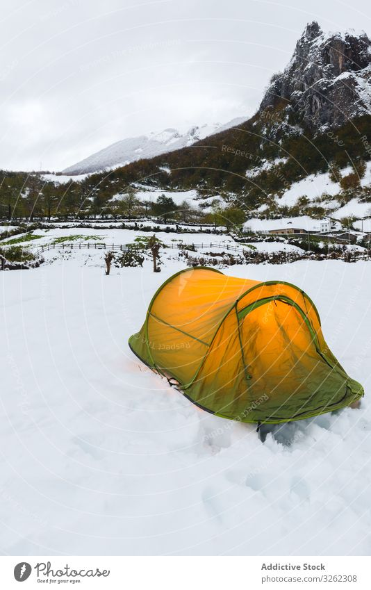 Tourist tent in mountains on snow tourism forest adventure travel nature landscape camp winter hiking cold trekking activity explore hill climb green light