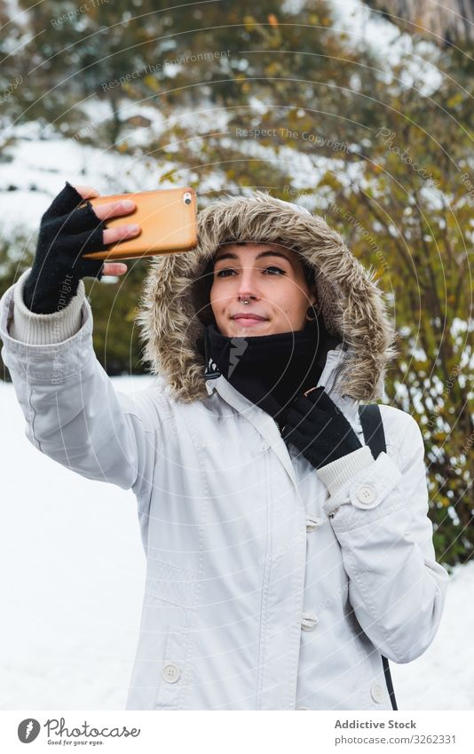 Woman taking selfie on nature at winter woman mobile phone smile content snow bush female smartphone walk rest holiday environment young happy active lifestyle