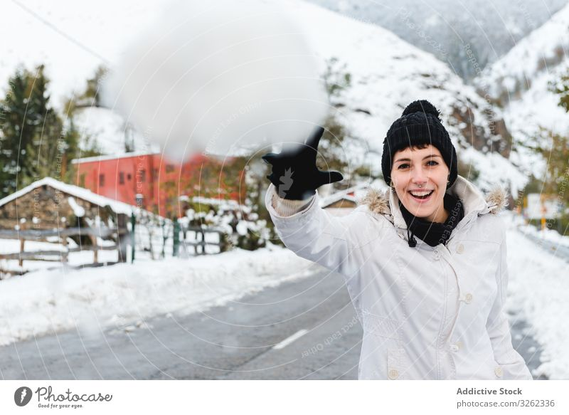 Smiling woman playing with snow in countryside snowball winter smile joy mountain rest resort holiday nature village rural cold fun game vacation tree white