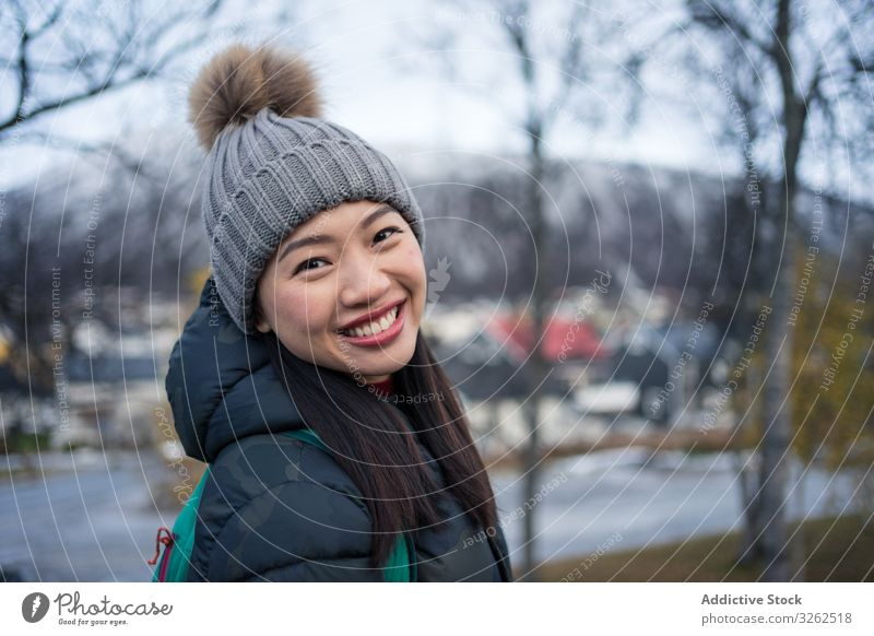 Joyful ethnic tourist on road bridge against modern building with unusual architecture at foothill in cold weather street church happy woman smile travel