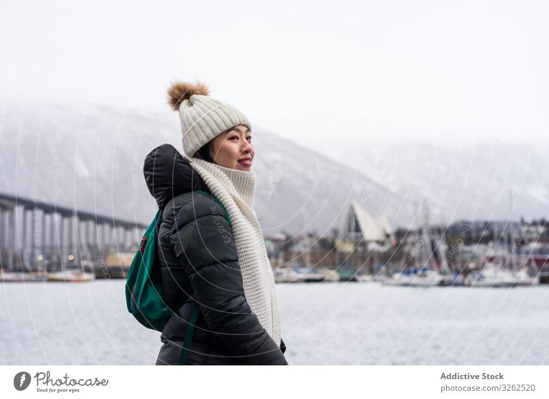 Asian female tourist in warm wear at snowy field near city tourism walking winter woman clothing travel building town holiday asian sightseeing skyline relaxing