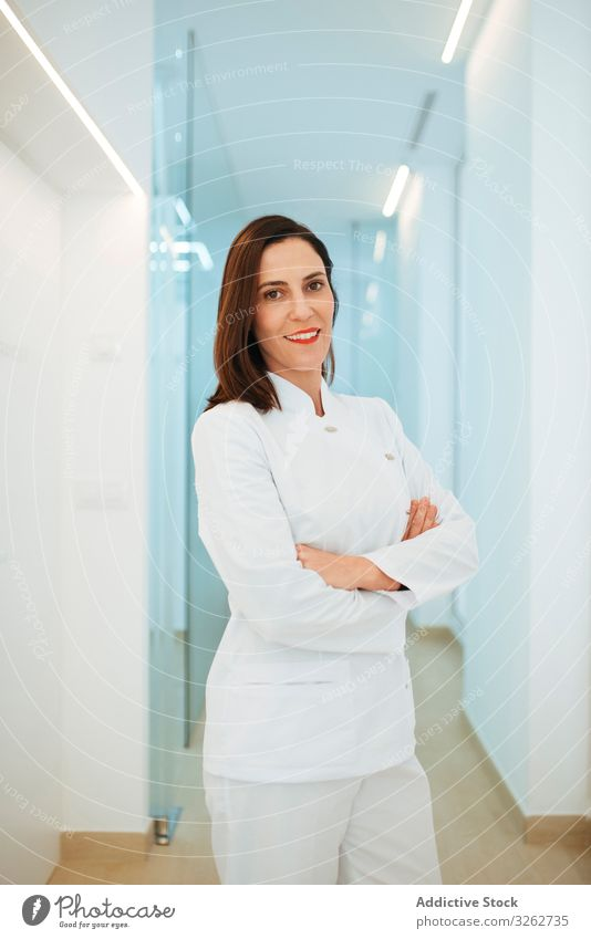 Confident dentist in white uniform with crossed arms looking at camera doctor smiling confident dental clinic medical medicine hygiene dentistry visit hospital
