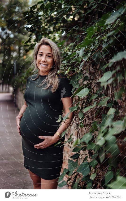 Charming pregnant woman standing on walkway in park path summer happy smile dress nature green forest trees wood road pathway female mother fertility expecting