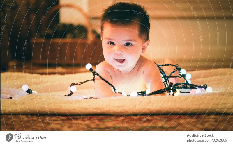 Baby playing with light garland on Christmas Day baby christmas colorful cozy evening carpet floor cute adorable child kid happy joy holiday winter december