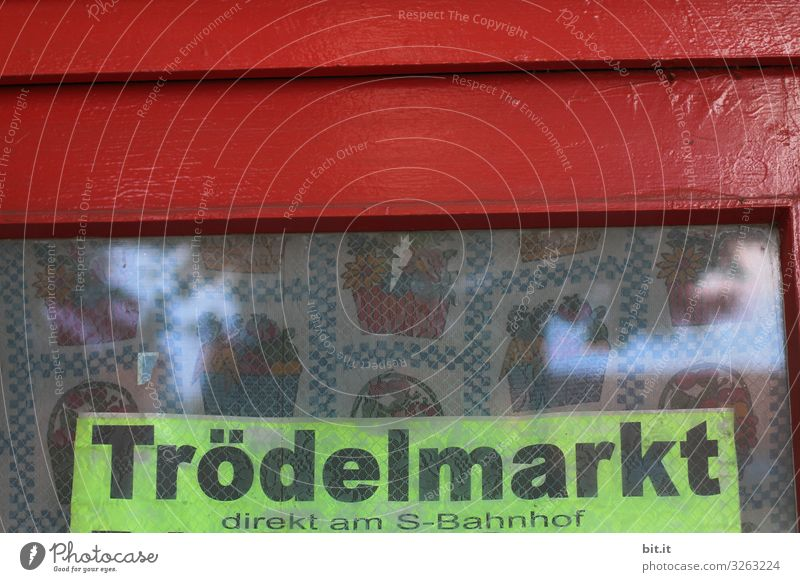 Black, thick lettering: flea market, written on sign in neon, hangs in old window, with red frame and nostalgic curtain, behind the window pane, as advertisement, hint, announcement, program for a flea market at the S-Bahn station in the city.
