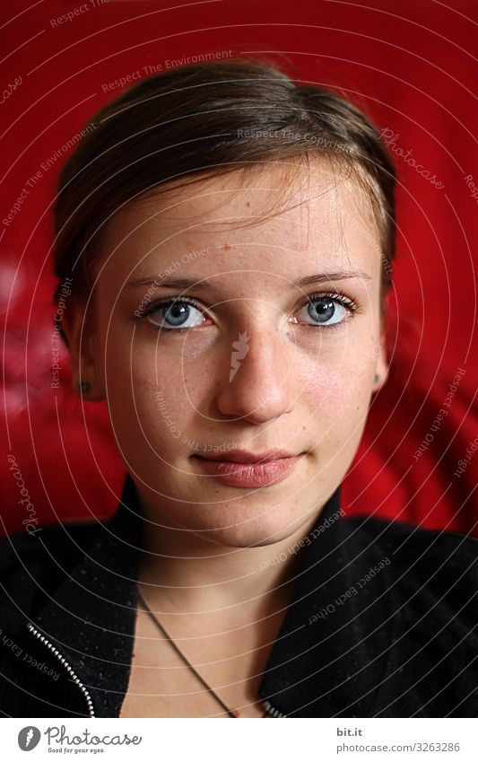 Young woman, girl, teenager with make-up, smiling, in front of a red background looking forward into the camera. Human being Feminine Youth (Young adults) Head