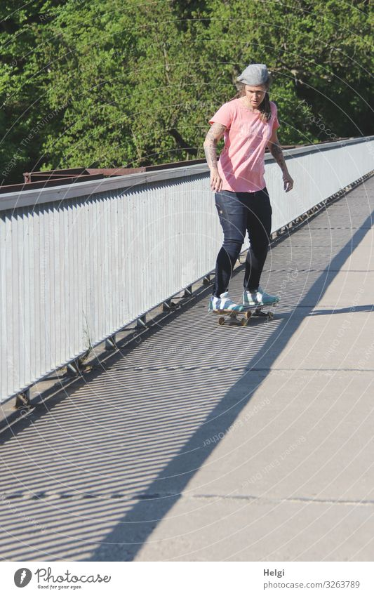 sporty lady rides her scateboard onto a bridge, the railing throws shadows Sports Fitness Sports Training Skateboard Human being Feminine Woman Adults 1