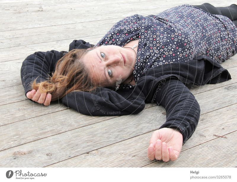 Woman with long brunette hair and dark and patterned clothes lying on a wooden floor Human being Feminine Adults 1 45 - 60 years Clothing Dress Jacket Brunette