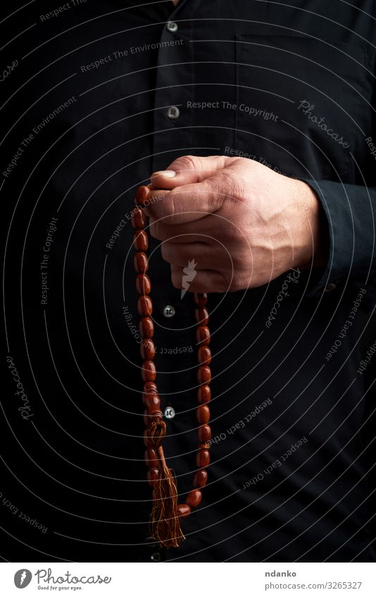 man in a black shirt holds a brown stone rosary Meditation Human being Man Adults Arm Hand Fingers Culture Brown Black Trust Hope Religion and faith handle