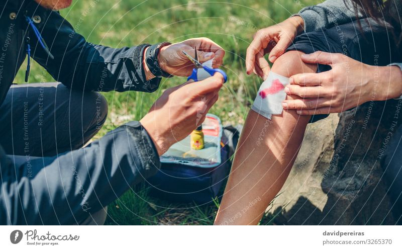 Man healing knee to woman who has been injured trekking Lifestyle Mountain Hiking Scissors Human being Woman Adults Couple Nature Autumn Forest Sit Authentic
