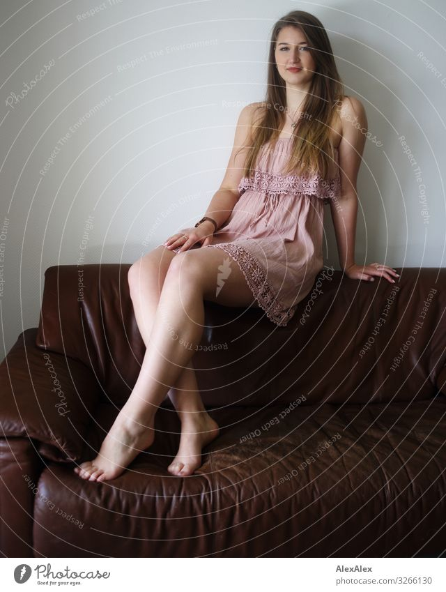 Portrait of a young woman on a brown couch Elegant Style Joy already Life Sofa Room Young woman Youth (Young adults) Legs 18 - 30 years Adults Dress Barefoot