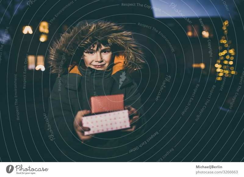 Boy with gifts in winter jacket Winter Christmas & Advent Child Human being Masculine Boy (child) 1 3 - 8 years Infancy Joy Gift Cold Jacket Street Blur Light
