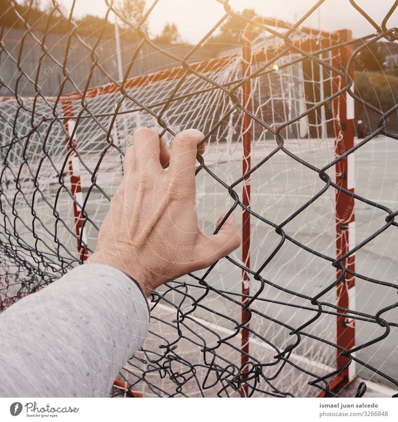 man hand grabbing a metallic fence Human being Man Hand Street Freedom Metal Arm Fingers Protection Fence Steel Safety (feeling of) Wire