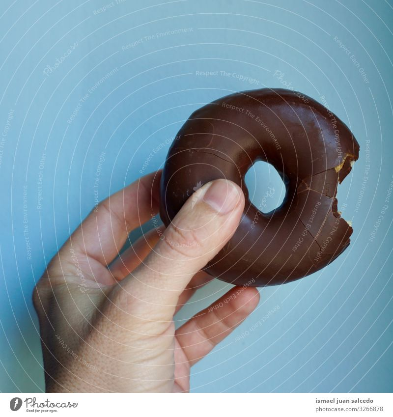hand with a delicious chocolate doughnut Blue Hand Food photograph Sweet Fingers Delicious Dessert Chocolate Appetite Donut Tasty