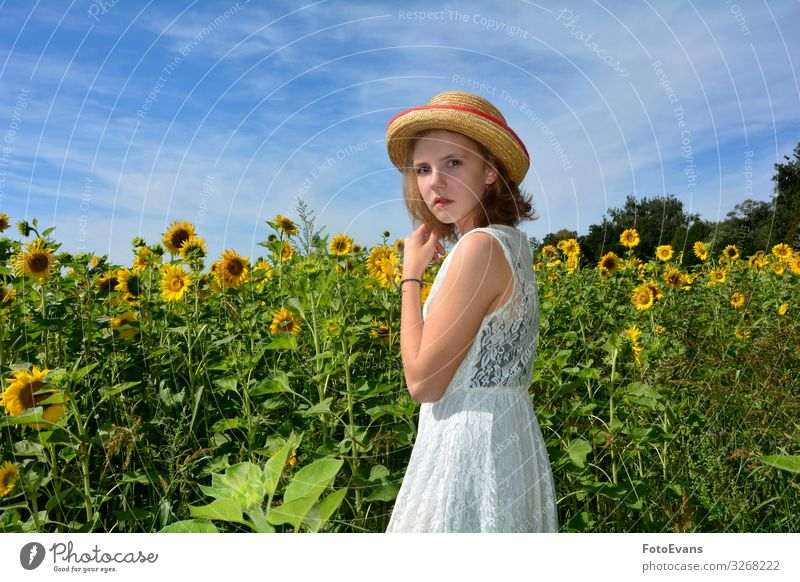 Young girl stands in front of a field of sunflowers Lifestyle Summer Feminine Girl Young woman Youth (Young adults) 1 Human being 13 - 18 years Nature Sky