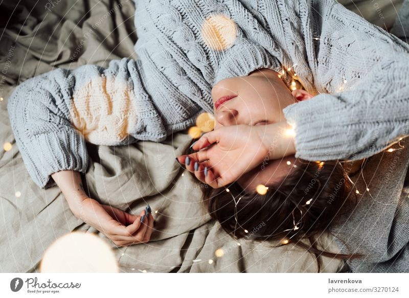 woman lying in bed with fairy Christmas lights and bokeh Bed Bedclothes Blur Caucasian Christmas & Advent Comfortable Cozy Evening Fairy lights Hand