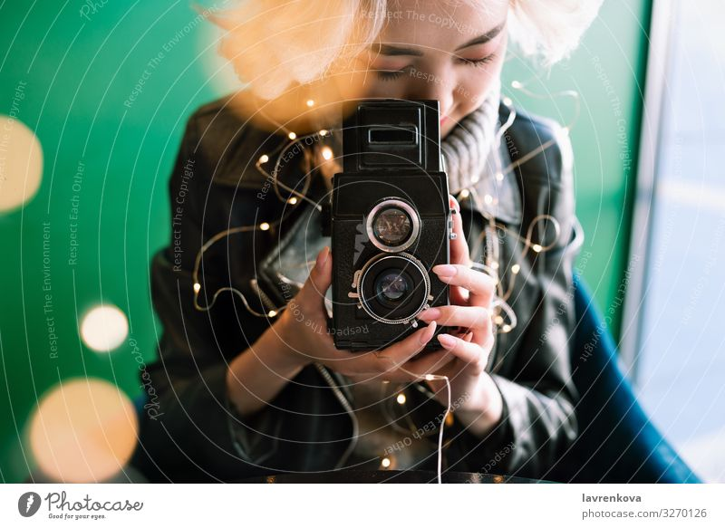 Female holding vintage film camera with fairy lights and bokeh Vintage Asians Café Lifestyle Film Portrait photograph Focus on Retro Human being Hand