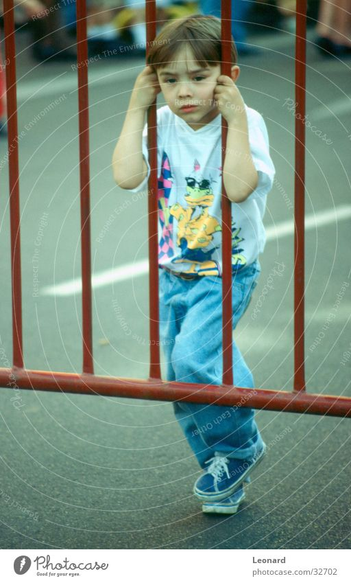 Human being Child Street Boy (child) Curiosity Fence Grating