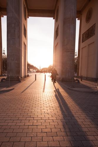 Brandenburg Gate at sunset with anonymous cyclist Life Berlin Tourist Attraction Landmark Bicycle Driving Germany City Back-light Column Transport Cycling
