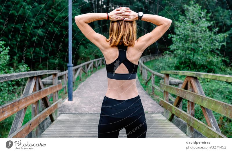 Unrecognizable sportswoman doing stretching arms outdoors Lifestyle Wellness Sports Human being Woman Adults Arm Nature Park Fitness Athletic Thin Backwards Top