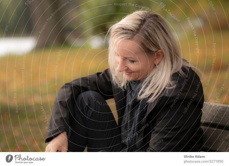 Woman sitting relaxed on a bench with a smile on her face and reading - UT Hamburg Face of a woman smilingly Blonde blonde hair Long-haired black clothes Soft