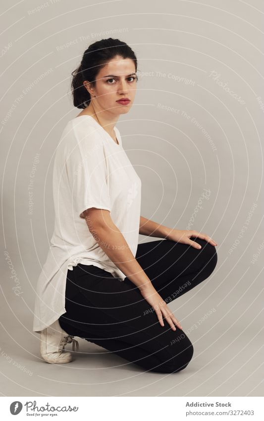Thoughtful young woman squatting in studio thoughtful crouch appearance personality individuality complexion athletic female natural simplicity serious slim