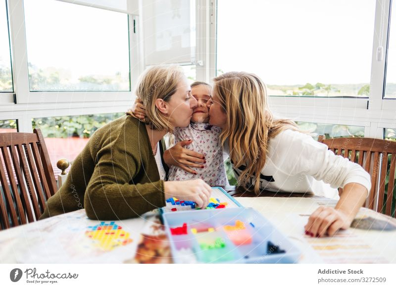 Woman playing board game with daughter and granddaughter family multi generational mother daughters together fun happy grandmother woman girl table female child