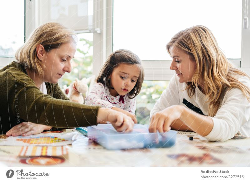 Woman playing board game with daughter and granddaughter family multi generational mother daughters together fun happy grandmother woman girl table piece female
