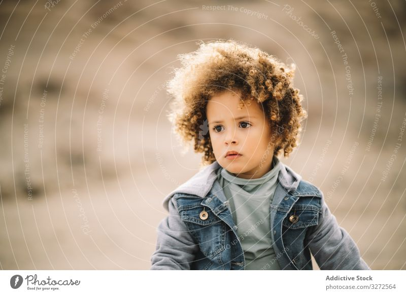 Ethnic curly toddler on nature child concentration pensive adorable focused wind girl casual human face portrait headshot appearance charming ethnic cute think