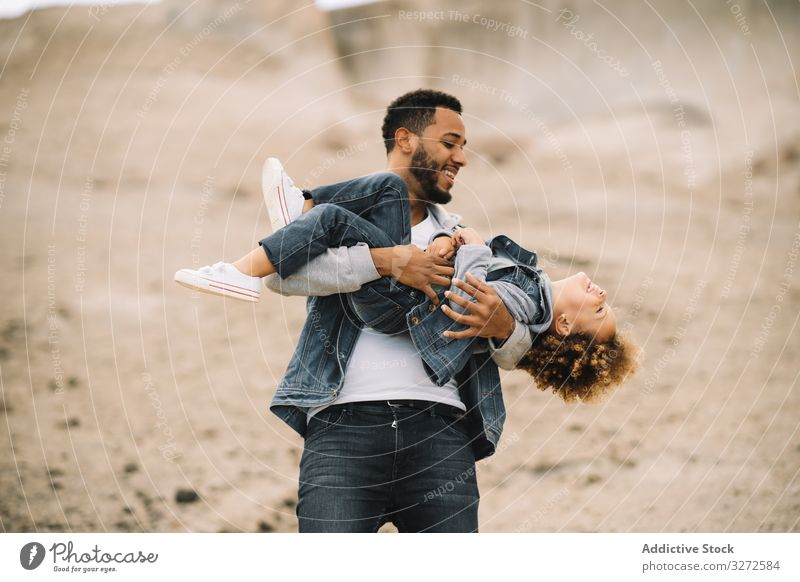 Ethnic father playing with child on ground toddler fun rest sand hill smile parent happy cheerful lifestyle modern nature dad man horizontal bonding love tender