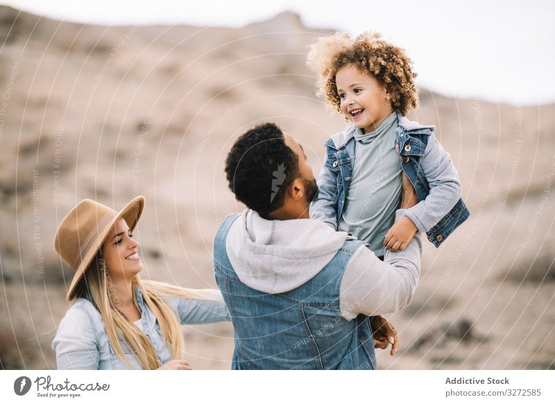 Happy multiethnic family gathering on nature fun parent toddler play rest sand smile happy cheerful lifestyle modern child man bonding love tender casual kid