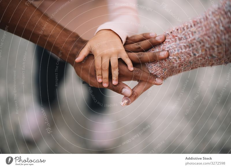 Hands of multiracial family putting together hands together diverse parent child alliance toddler generation mutual aid care unity happy support love joint team