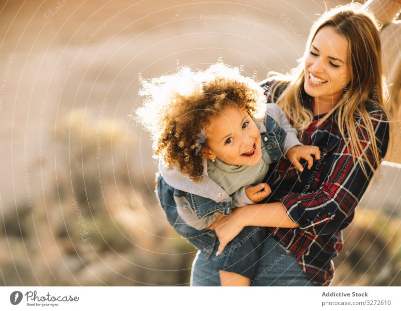 Cheerful woman play with toddler on nature child cuddle hold embrace smile happy tickle cheerful expression curly hair indulge mother fun rest parent lifestyle