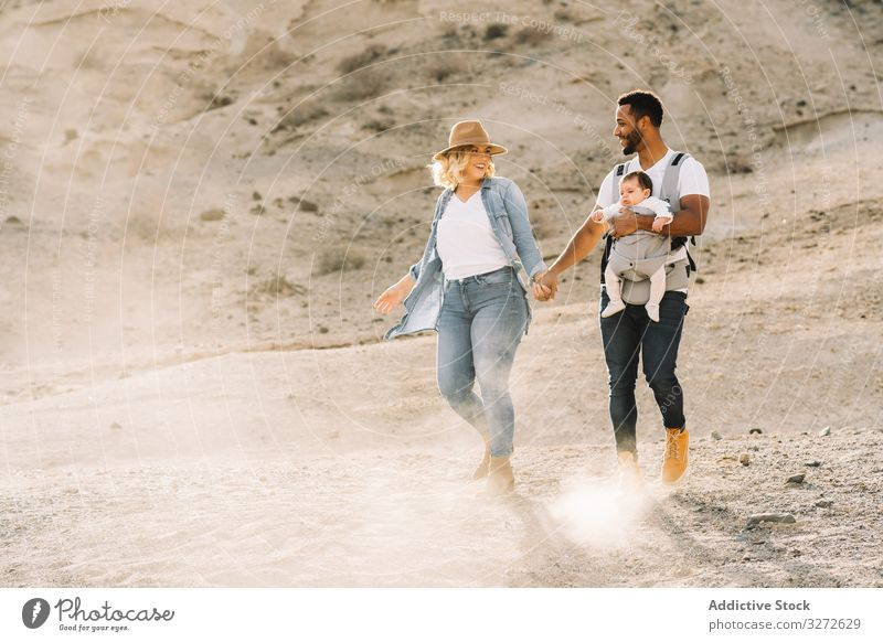Diverse parents dancing while walking with baby dance family happy smile sand desert carry fun nature newborn cheerful lifestyle modern child wife bonding love