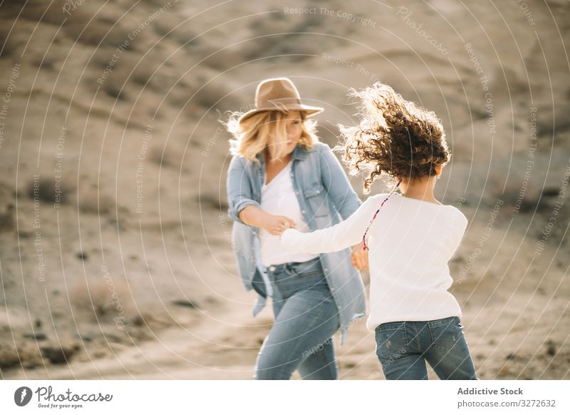 Mother dancing with girl on nature mother spin parent fun dance vacation daughter happy smile sand desert walk cheerful lifestyle modern child bonding love