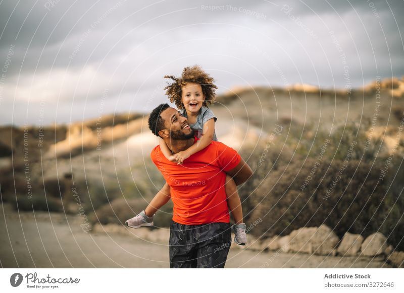 Black father holding child in arms toddler carry sportive smile play fun rest parent happy cheerful lifestyle modern nature man bonding love tender casual kid