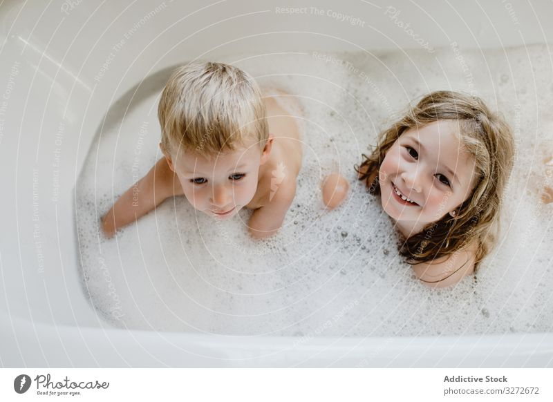 Funny children playing with foam in bath family innocence small bathing wet siblings together healthy brother bubble water laughing growth hygiene naked fun