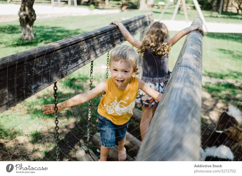 Funny children climbing on playground in summer day adventure having fun playful meadow siblings tree childhood nature bridge park active lawn girl boy