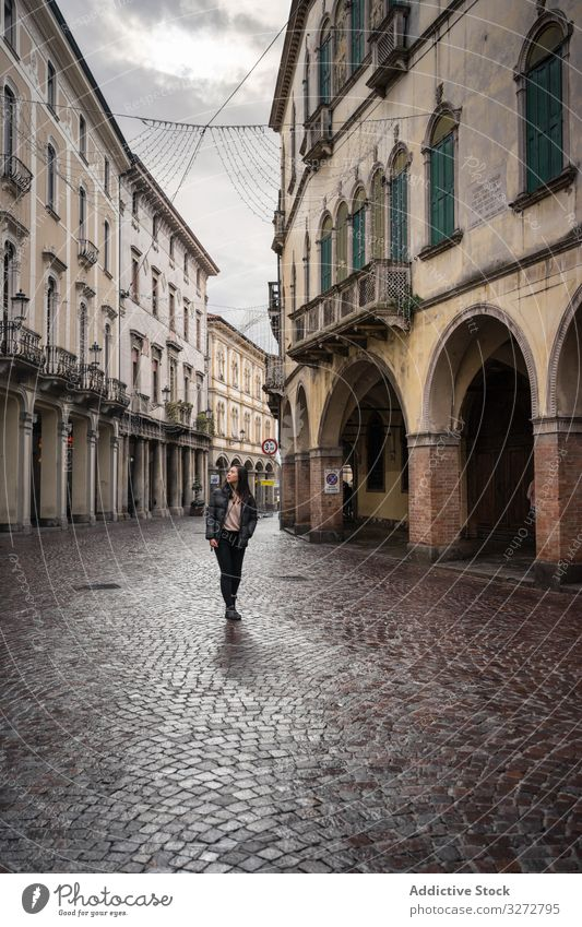 Curious female tourist strolling at old city street on overcast weather tourism walking ancient aged curious explore architecture building journey vacation