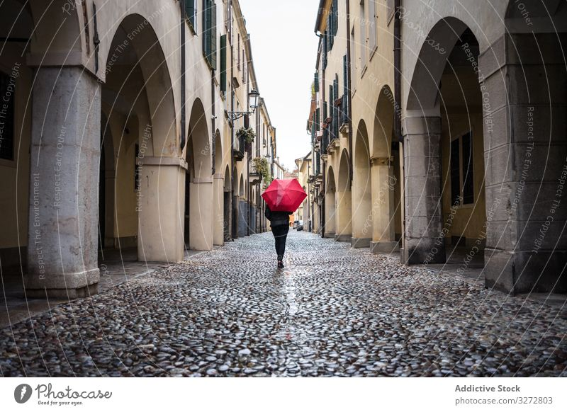 Tourist with umbrella walking at city street on rainy weather person tourist strolling explore interest wet building old beautiful architecture travel