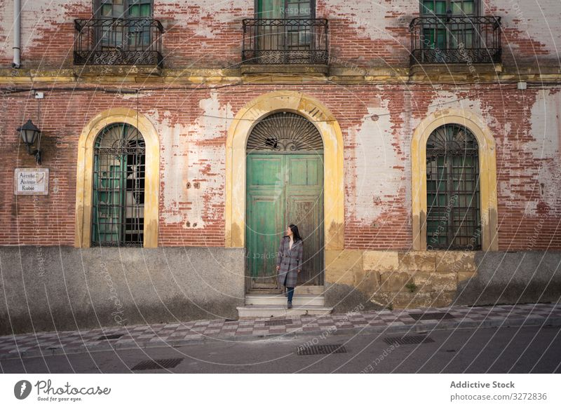 Woman on street with aged building woman spain travel antique malaga carratraca historical facade lifestyle freedom holiday journey adventure vintage exterior
