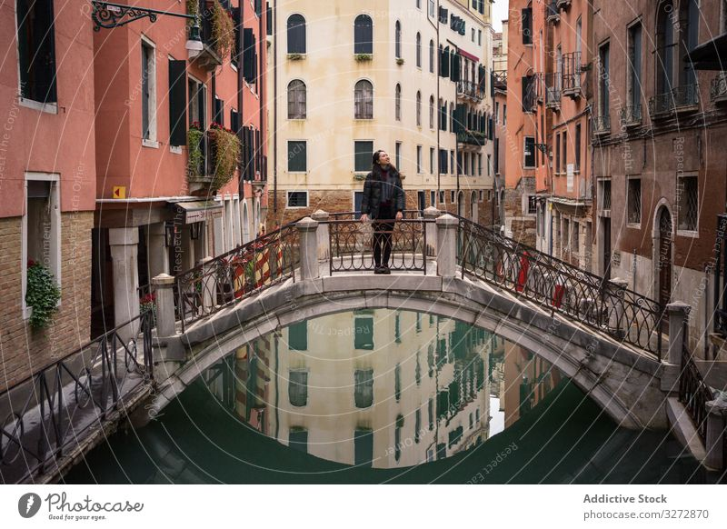 Satisfied resting woman delighting in vacation on small bridge above waterway tourism city canal building old historical standing fun architecture enjoy smile