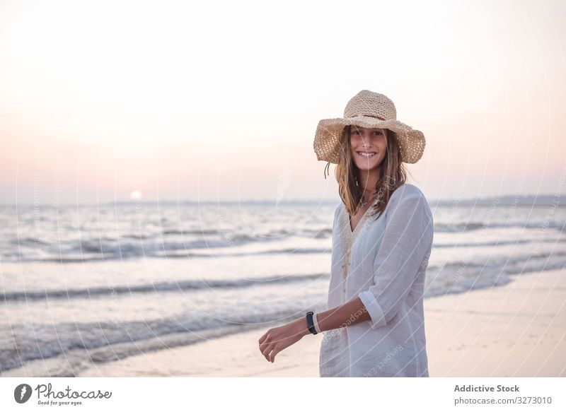 Charming woman in light white dress on wavy beach sea traveling seaside tourism charming vacation hat curly holiday summer freedom journey young relaxing