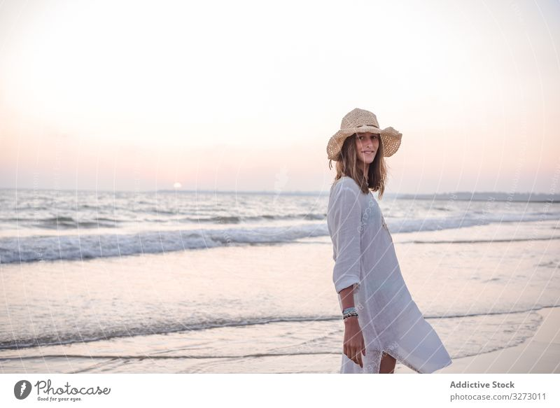 Charming woman in light white dress looking at camera over shoulder on wavy beach sea traveling leaning seaside tourism charming vacation hat curly holiday