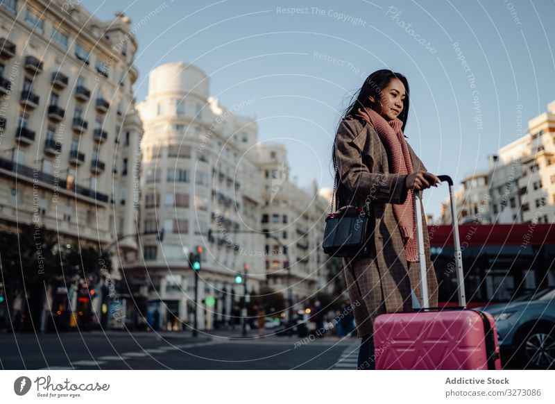 Asian tourist on sidewalk in city woman suitcase road ethnic smile sunny daytime female visit street asian luggage baggage travel trip young urban town pavement