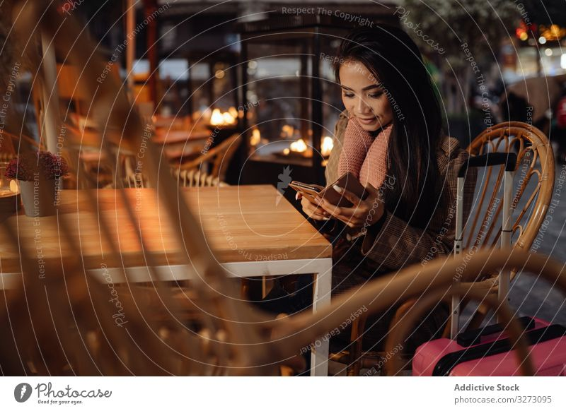 Asian traveler using smartphone in cafe woman tourist suitcase ethnic evening city urban female asian browsing social media casual smile cheerful glad