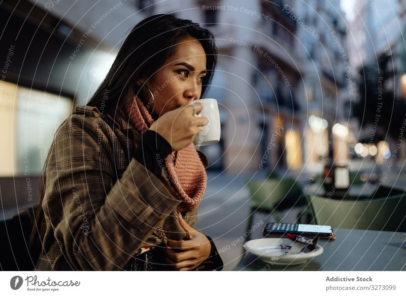 Asian woman enjoying hot beverage in street cafe drink evening city urban sip cup ethnic female young stylish trendy coffee tea lifestyle rest relax lady asian