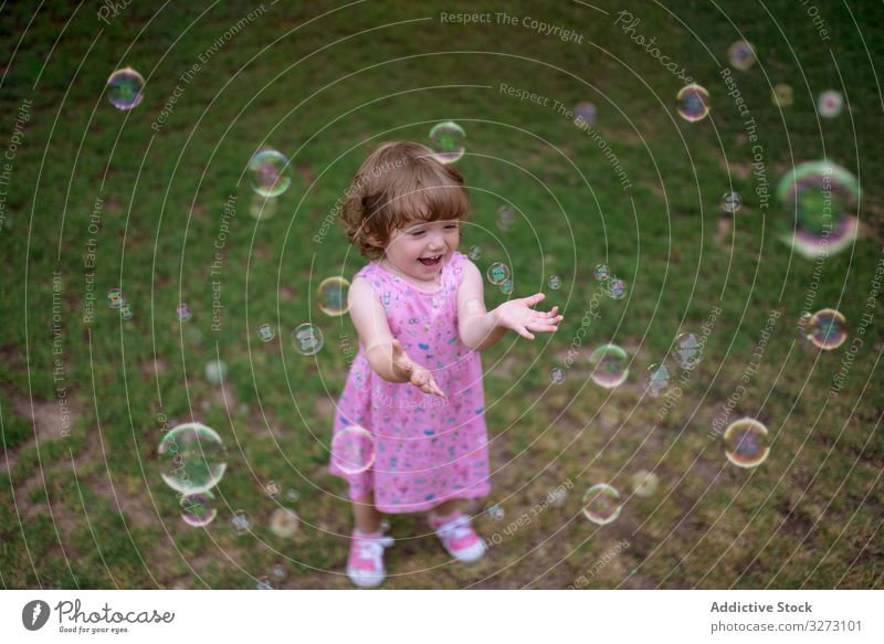 Joyful girl playing with colorful bubbles in grass soap childhood joyful fun adorable cheerful park playful enjoyment action wet little motion recreational blow