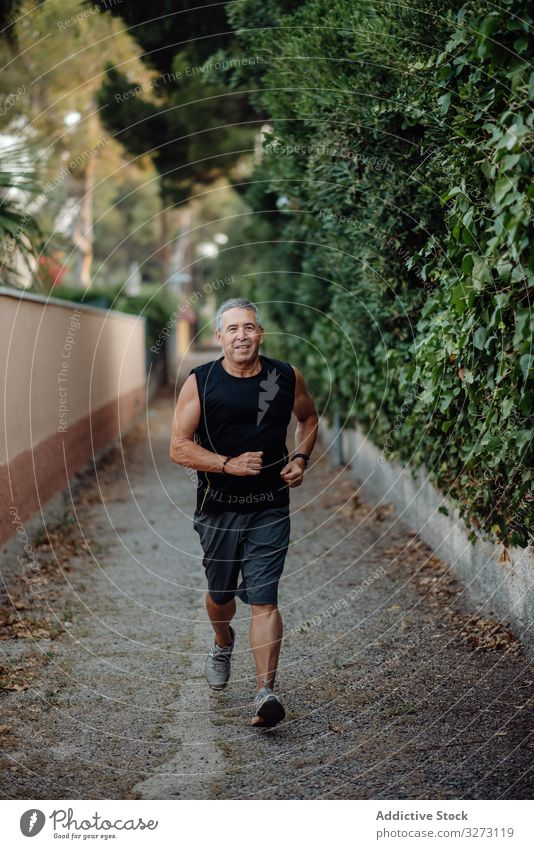 Old man in good shape running on road along plant fence sportive jogging elderly street mature old training runner athlete workout fitness city healthy athletic